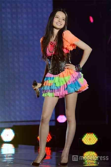 カラフルな衣装を着て笑顔で舞台に立つベッキー