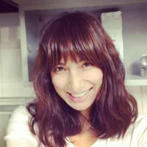 白いトップスを着て笑っている佐田真由美の画像