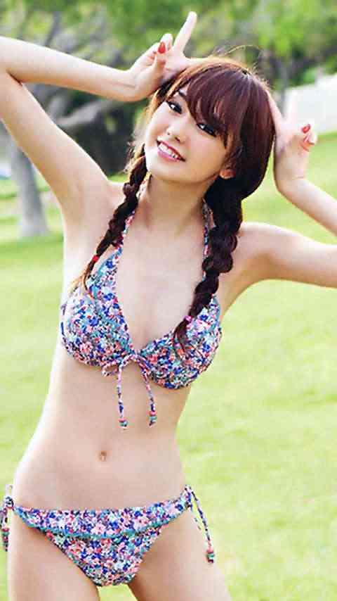 鮮やかな水着を着て両手でピースをする桐谷美玲