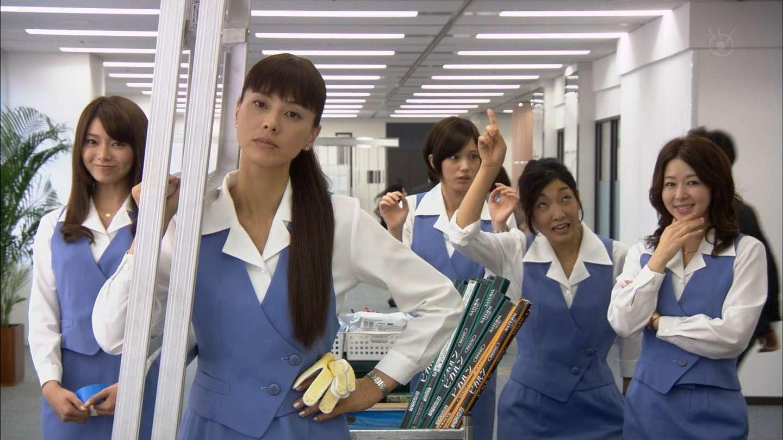 ショムニの制服で顎を手で触りながら微笑む堀内敬子