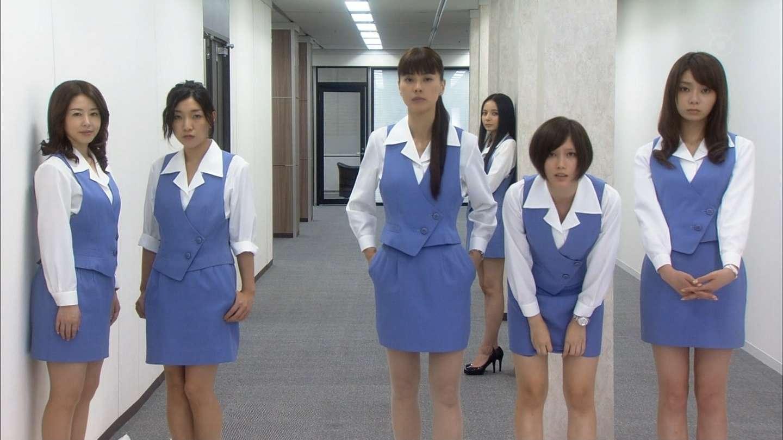 ショムニの制服で微笑みながら壁際に立つ堀内敬子