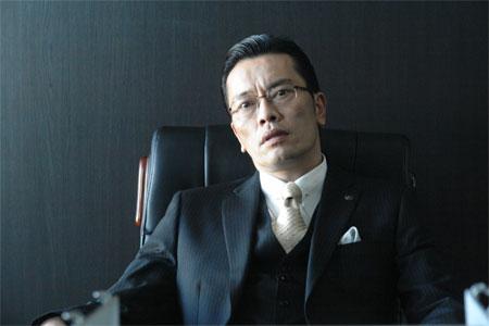 椅子に座る遠藤憲一