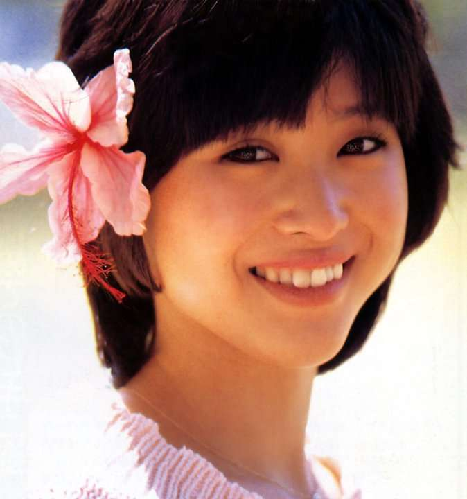 頭に花を飾って嬉しそうに笑顔を見せる松田聖子