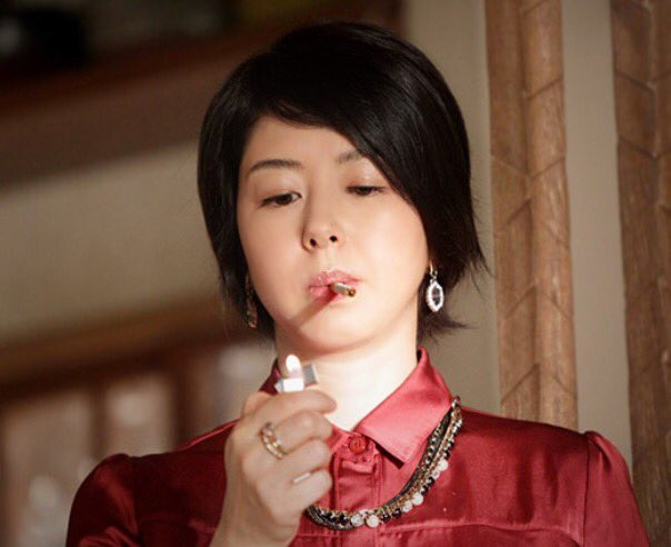 たばこに火をつける堀内敬子