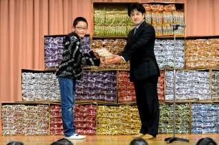 コンテストでグランプリを獲得した男性 賞品のうまい棒1万本を児童に寄付